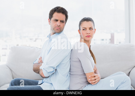 Angry couple sitting back to back on the couch - Stock Photo