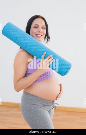 Pregnant woman holding exercise mat smiling at camera - Stock Photo