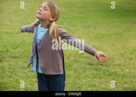 Girl with arms outstretched at park - Stock Photo