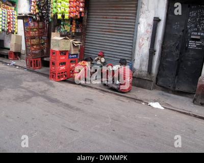 Streets of Kolkata. Poor family eats on the street. - Stock Photo