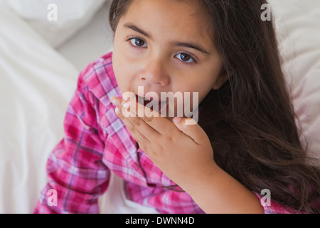 Close-up of a young girl yawning in bed - Stock Photo