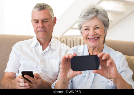 Senior couple sitting on couch using their smartphones - Stock Photo