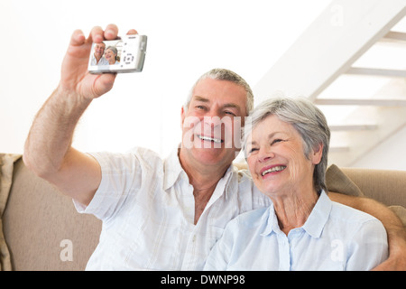 Senior couple sitting on couch taking a selfie - Stock Photo