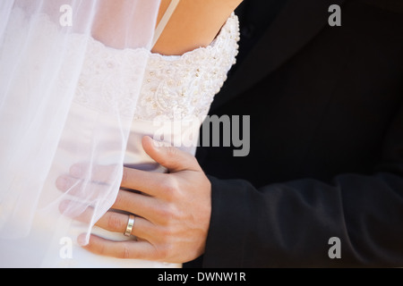 Mid section of newlywed couple embracing - Stock Photo