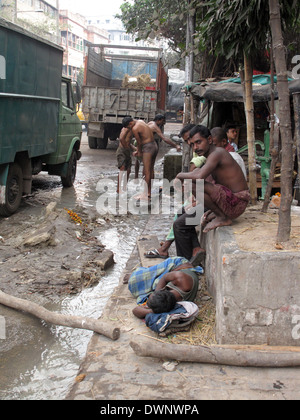 Streets of Kolkata. Indian people wash themselves on a street , January 25, 2009. - Stock Photo