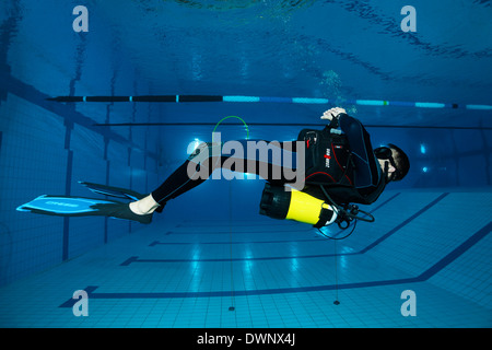 Dive training, scuba diver facing the surface, balancing, in a swimming pool, Nuremberg, Bavaria, Germany - Stock Photo