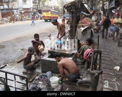 KOLKATA, INDIA -JANUARY 25: Streets of Kolkata. Indian people wash themselves on a street , January 25, 2009. - Stock Photo