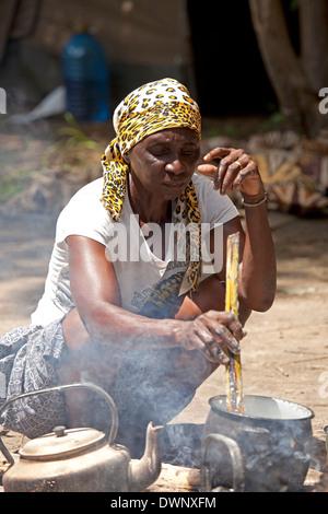 Kavango woman preparing the traditional Ugali maize flour dish on a campfire, Okavango Delta, Botswana - Stock Photo