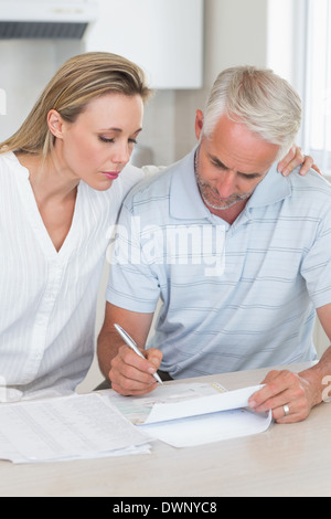 Serious couple working out their finances - Stock Photo