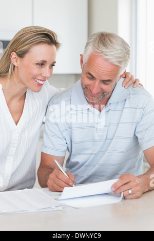 Happy couple working out their finances - Stock Photo