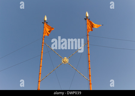 Top part of Nishan Sahib at Golden Temple in Amritsar, the holiest site for Sikhism. These are triangular flags - Stock Photo