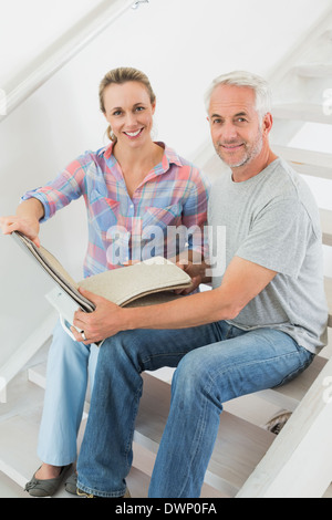 Happy couple picking out carpet samples together - Stock Photo