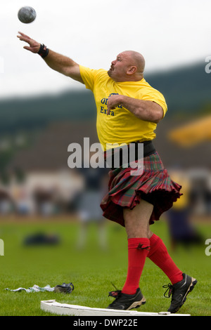Sportsman 'Putting the shot' at the Cowal Gathering Highland Games near Dunoon on the Cowal Peninsula in Scotland. - Stock Photo