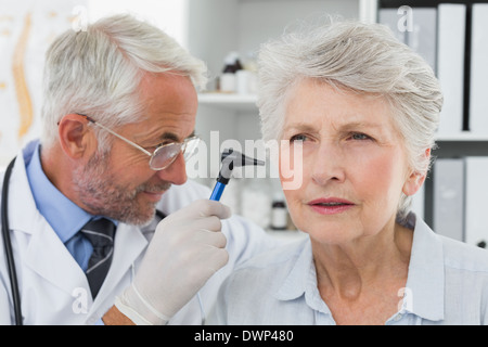 Doctor examining senior patient's ear - Stock Photo