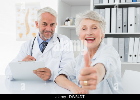 Happy senior patient gesturing thumbs up with doctor - Stock Photo