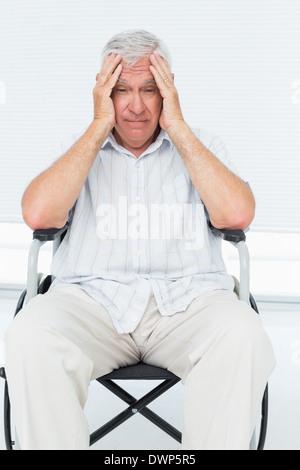 Sad senior man sitting in wheelchair - Stock Photo