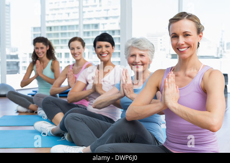 Class sitting with joined hands in row at yoga class