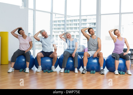 Class sitting on exercise balls and stretching neck in gym - Stock Photo