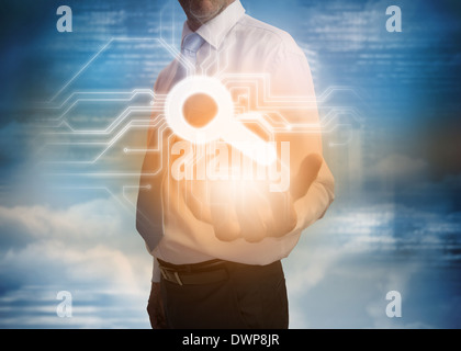 Businessman presenting magnifying glass graphic - Stock Photo