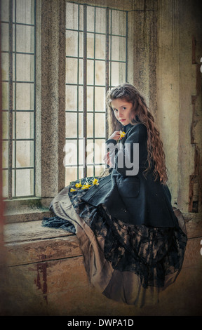 Victorian girl with daffodils in spring sitting on the windowsill in an old building - Stock Photo