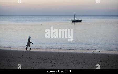 Inhaca Island, Mozambique. 23rd Feb, 2013. A boat lies off Inhaca Island as a woman walks barefoot along the beach - Stock Photo