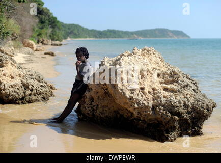 Inhaca Island, Mozambique. 23rd Feb, 2013. A child leans on a rock on a beach of Inhaca Island, Mozambique, 23 February - Stock Photo