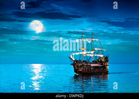 Old pirate ship sailing at Moon - Stock Photo