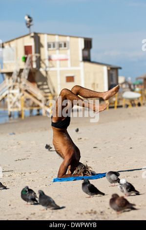 Man practices yoga on beach in Tel Aviv Israel - Stock Photo