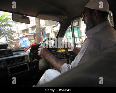 Taxi driver its way through the dense traffic jams on a busy street in Kolkata, India - Stock Photo