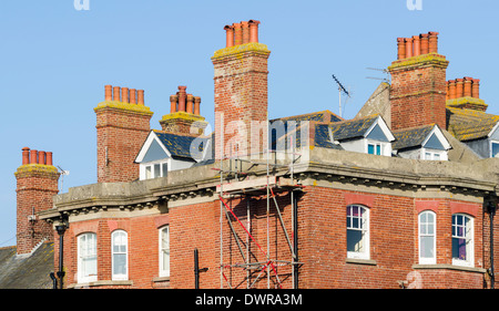 Several chimneys and chimney pots on high brick chimney stacks on Victorian housing in England. - Stock Photo