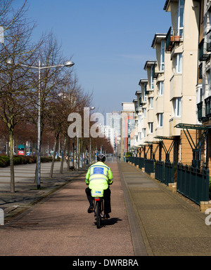 Police Community Support Officer on bicycle, Lloyd George Avenue, Cardiff Bay, Wales. - Stock Photo