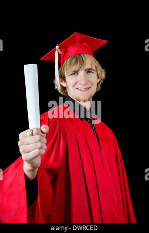 Handsome high school graduate wearing a red cap and gown isolated on black holding a diploma - Stock Photo