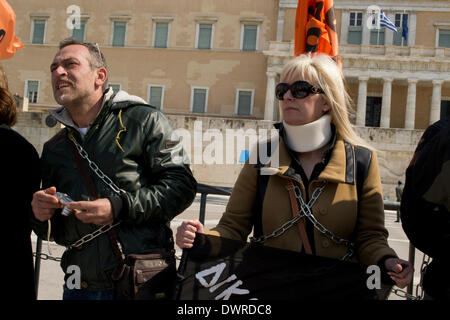Athens, Greece, March 12th, 2014. Teachers are tied up with chains in front of the Greek Parliament, as public sector - Stock Photo