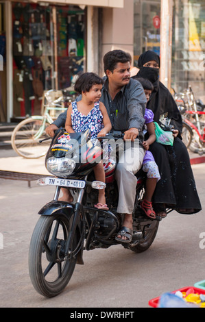South Southern India Tamil Nadu Madurai street scene Muslim family 4 four on motorbike mother father 2 two children - Stock Photo