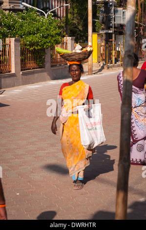 South Southern India Tamil Nadu Madurai street scene lady woman female basket pannier fresh vegetables on head yellow - Stock Photo