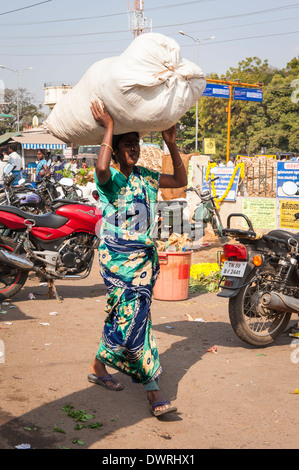 South Southern India Tamil Nadu Madurai flower market woman lady female in green sari saree carries white sack on - Stock Photo