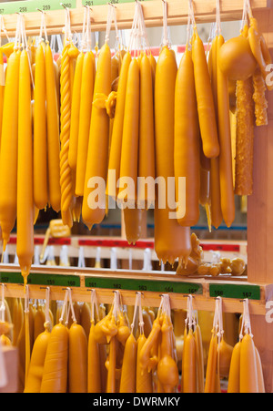 A variety of handmade candles of beeswax are hanging off the shelf in a chandler's workshop. - Stock Photo