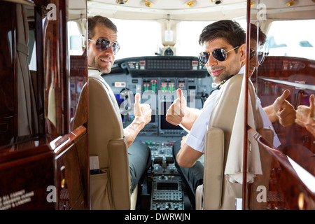 Pilots Gesturing Thumbs Up In Cockpit - Stock Photo