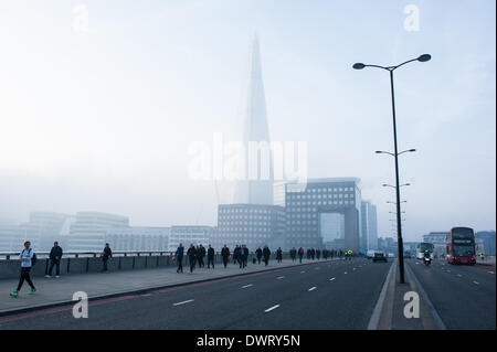 London, UK. 13th March 2014. morning commuters on London Bridge as London wakes up under heavy fog Credit:  Piero - Stock Photo