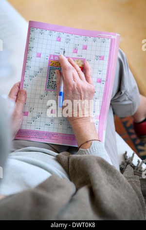 Elderly person doing cr-word puzzle - Stock Photo