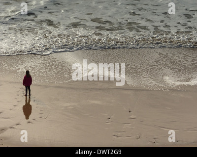 A little girl standing on the beach looking out to sea - Stock Photo
