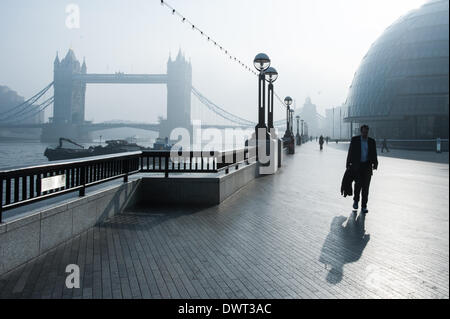London, UK. 13th March 2014. A man walks near Tower Bridge as London wakes up under heavy fog. Credit:  Piero Cruciatti/Alamy - Stock Photo