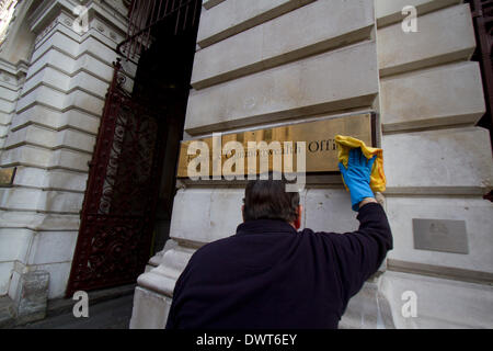 Westminster London, UK.13th March 2014. A worker polishes the brass plaque at the Foreign and Commonwealth Office - Stock Photo