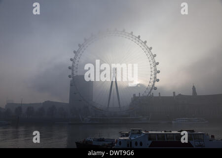 LONDON, UK, 13th Mar, 2014. London starts the day swathed in a blanket of fog. The sun rises above County Hall, - Stock Photo