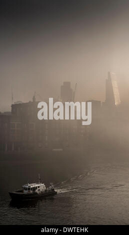 The City Skyline can just about be seen in this morning's heavy fog over London, Looking from the Millennium Bridge - Stock Photo