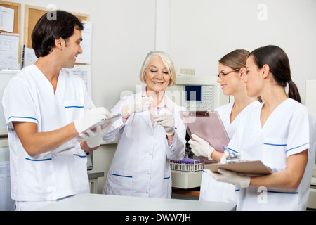 Scientists Discussing Over Sample In Laboratory - Stock Photo