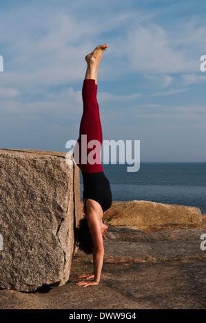 Iyengar ® Yoga Instructor Demonstrates Adho Mukha Vriksasana (Inverted). - Stock Photo