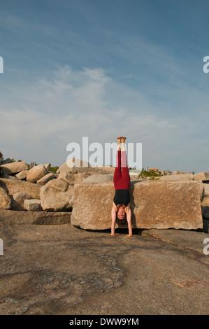 Iyengar Yoga Instructor Demonstrates Adho Mukha Vriksasana (Inverted). - Stock Photo