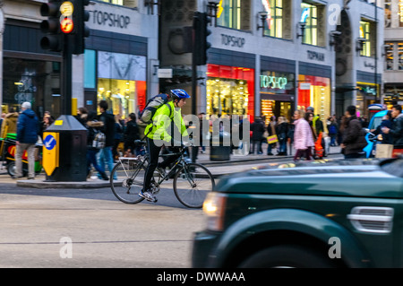 Cyclist going through Oxford Circus, London - Stock Photo