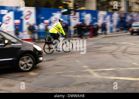 Policeman on Bicycle is Turning Right into Tottenham court Road coming from New Oxford Street, London. - Stock Photo